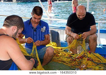 BALI, CRETE - SEPTEMBER 16, 2016 - Three Cretan fishermen tending to their fishing nets on a small fishing boat in the harbour Bali Crete Greece Europe, September 16, 2016.