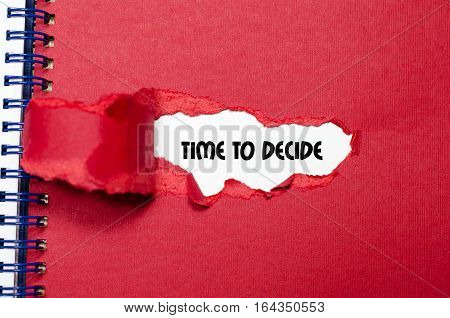 The word time to decide appearing behind torn red paper
