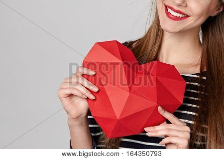 Cropped image of woman with red lips holding red polygonal paper heart shape with flying hair