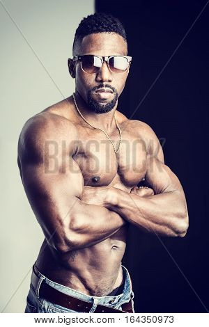 African American bodybuilder man, naked muscular torso, wearing jeans, on dark background