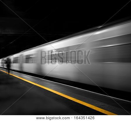 Passenger running to catch departing train against a partly desaturated black background