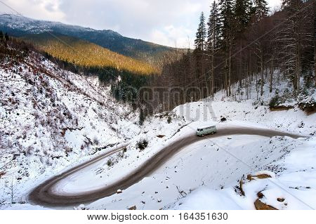 The car in the winter riding down the mountain winding road. The road to the mountain Dragobrat Western Ukraine.