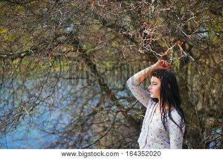 Wonderful portrait of beautiful long-haired girl with silky hair braided in pigtail a light sweater meditating on the shore of lake placing his hand on head background of branches with blossoming buds