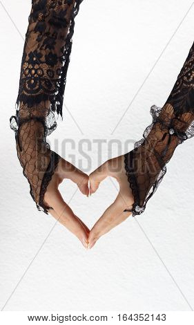 Two beautiful female hands in black lace gloves and dress form heart against white background. Valentine's day and love concept