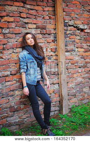 Young pretty girl with long brown hair dressed in a denim jacket pants and black scarf looks pensive standing near a brick wall on the street.