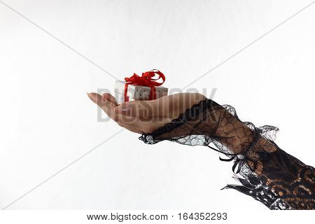 One beautiful female hand in black lace glove holds a gift box with red ribbon against white background. Valentine's day and love concept