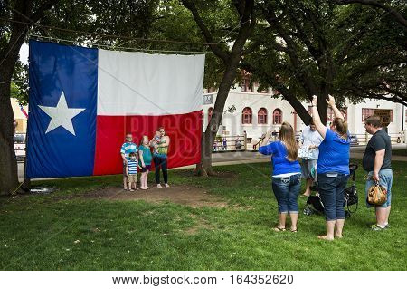Fort Worth Texas USA - June 10 2014: Family taking a photo in front of the Texas Flag in the Fort Worth Stockyards Forth Worth Texas