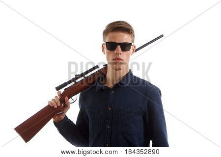 A young adult in a shirt holding a rifle on his shoulder