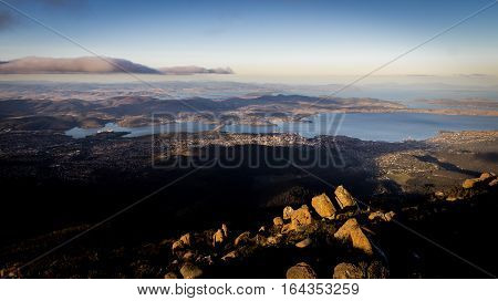 View from Mount Wellington overlooking the city of Hobart, Tasmania, Australia with rocks in afternoon light