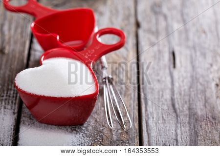 Baking sweets for Valentines day, sugar in red heart shaped measuring cups