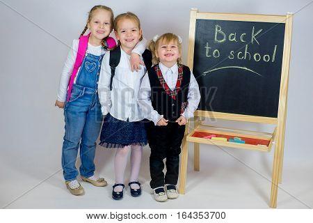Three Young Schoolgirls Near The Blackboard