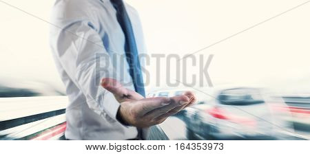 Businessman holds out his hand with background traffic of cars
