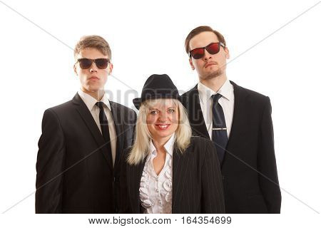 A smiling woman with two young adults in suits