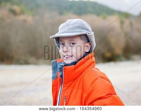 cute young boy in a cap in the autumn