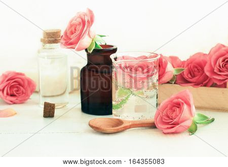Rose cosmetic ingredients for herbal spa beauty treatment. Flower in attar glass test jar with ml scale on wooden white table. Soft focus, soft light.