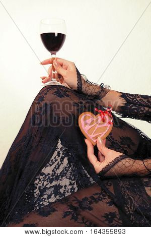 Female hands in black lace gloves hold heart shaped gingerbread cookie and glass of red wine body in black transparent lace dress incognito close up. Valentine's day and love concept