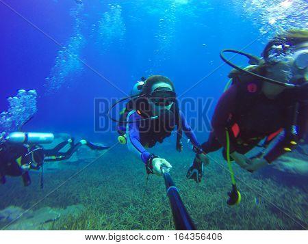 Underwater couple scuba diving selfie shot with selfie stick. Deep blue sea. Wide angle shot.