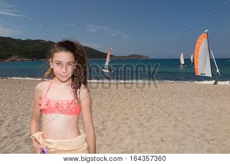 A Girl On Vacation At The Beach With Rental Boats In The Background