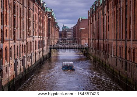 Tourist boat in famous Speicherstadt warehouse district with dark clouds in Hamburg, Germany
