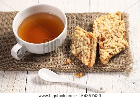 Cup of hot tea and homemade shortbread cookies with jam on white wooden table