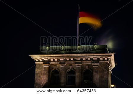 German flag flattering on Reichstag building, seat of the German parliament in Berlin, Germany