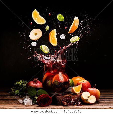 Sangria. Flying fruits. Apple, orange, lime, pomegranate, mint. Drink. Wine. Concept. Dark moody. Spain. Beverage jug. Wine or juice jar.