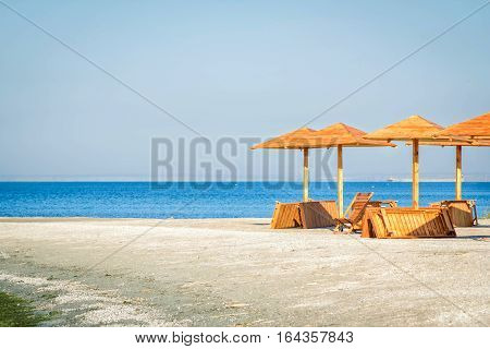 New wooden umbrellas, chair and sunbeds on the beach on a sunny day