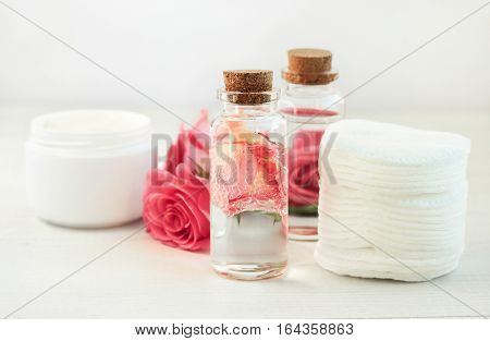 Facial lotion floral extract. Glass bottle with attar bubbles and rose petals, cotton pads. Healing homemade skincare moisture tonic. Gentle soft focus.