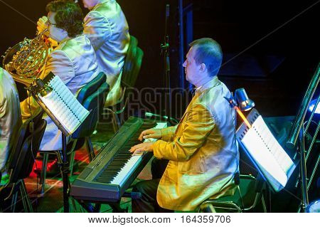 Tyumen, Russia - April 16, 2014: Competition of young performers the Song knows no limit in dramatic theater. Orchestra with musical instruments and performers during the performance