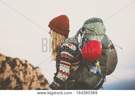 Woman Traveler with big backpack hiking Travel Lifestyle concept adventure active vacations outdoor wearing orange hat and sweater clothing