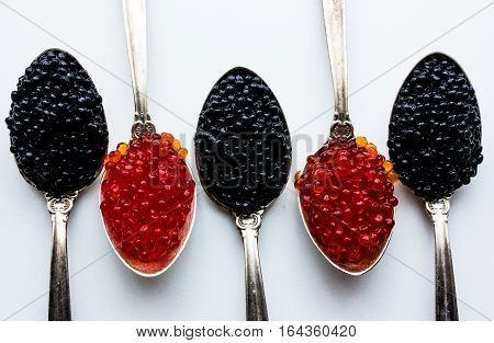 Red and Black caviar beads on silver spoon close-up isolated on white background.Top view