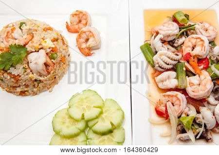 On an plate there is Thai food whit scampi