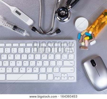 Medical doctor table desk with computer keyboard stethoscope thermometer medicine mouse and syringe. Flay layout.