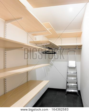 White cloakroom with beige shelves and ladder