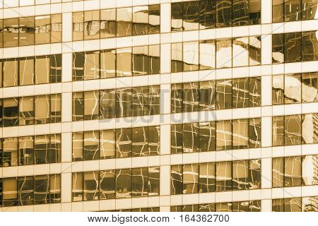 Close-up of the glass office building with reflections and sepia effect