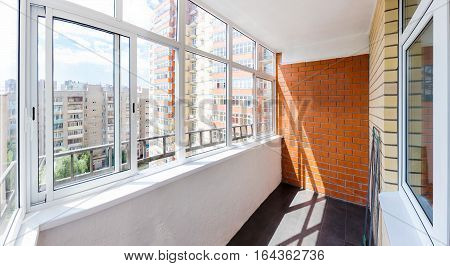 The new glazed balcony with brick wall