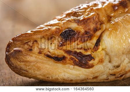 Close up of one cheese patty smeared with honey and sesame seeds on wooden background