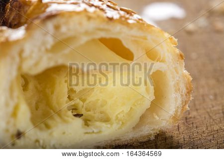 Interior of one cheese patty smeared with honey and sesame seeds on wooden background