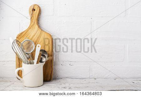 Kitchen tools, olive cutting board on a kitchen shelf against a white brick wall. selective focus