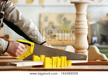Carpenter sawing a board with a hand saw