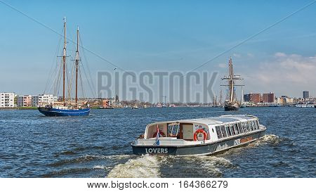 Amsterdam, Netherlands, April 10, 2016: Ships on the River IJ behind the Central Station of Amsterdam.