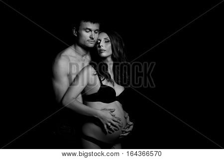Monochrome Portrait Of Happy Loving Couple In A Moment Of Love And Tenderness. Pregnant Woman With H