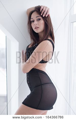 Beautiful and sexy brunette young woman wearing black lingerie in light room .Fashion shoot lingerie indoor .Sexy young girl in black lingerie in hotel
