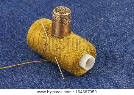 On a blue denim lies reel yellow thread with a needle and a metal copper thimble