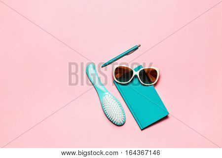Flat feminine composition of turquoise accessory: hairbrush, glasses, diary and pen isolated on pink copy space.