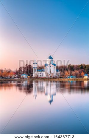 Alexander Nevsky Orthodox Christian Church With Bell Tower And Chapel On Lake Shore In Sunset Sunrise Dawn, Early Spring, Forest Park Background. Gomel, Homiel, Belarus
