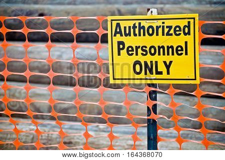bold sign saying authorized personnel only posted on orange fence