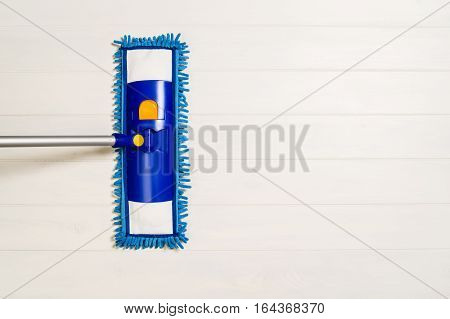 Cleaning floor with mop top view. Microfiber mop isolated on white wooden floor background. Home cleaning product concept photograph with copy space