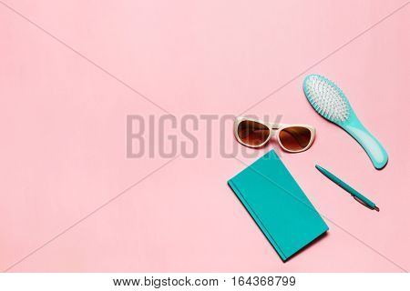 Feminine turquoise colored accessory of hairbrush, glasses, diary and pen isolated on pink copy space.