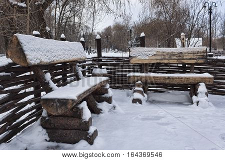 Stylized antique benches in the park. Winter all covered with snow